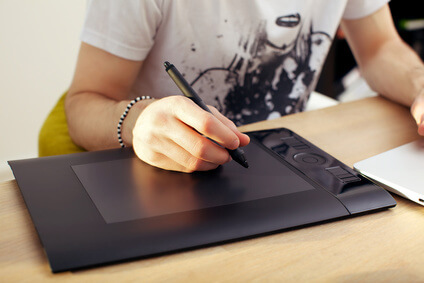 Closeup of a mans hand holding a pen stylus over a touchpad graphics tablet.